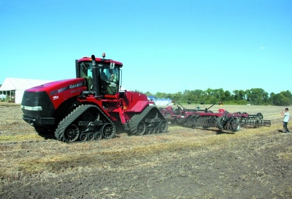 современный гусеничный трактор в поле