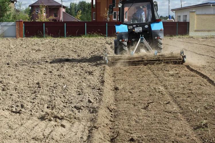 Разравнивания участка трактором
